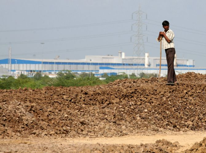 Govinda, 13, watches his cattle graze near the Tata Nano car plant in Sanand, Gujarat state.