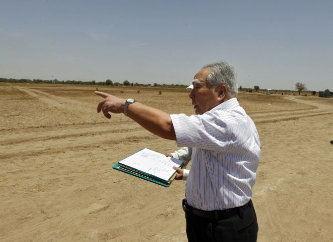 Suzuki Motor Corp's Osamu Suzuki gestures while checking a map during his visit to the construction site of a Maruti Suzuki plant at Vitthlapur village in the western Indian state of Gujarat.