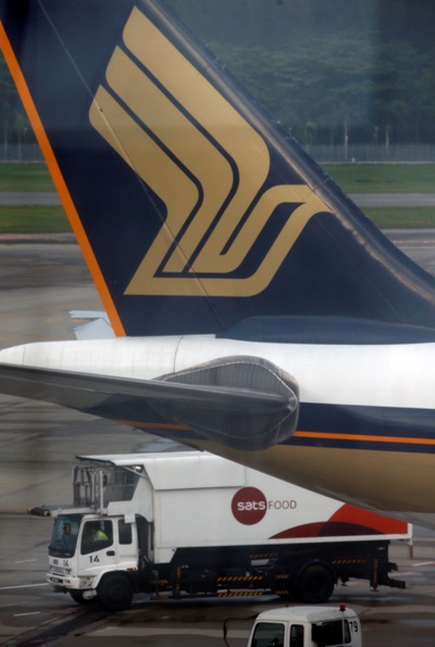 An in-flight catering truck passes a Singapore Airlines plane sitting on the tarmac.