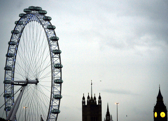 The London Eye is seen near the Houses of Parliament at dawn in central London.