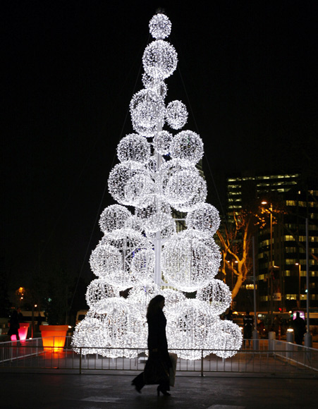 A woman walks past a Christmas tree in front of a shopping mall in Istanbul.