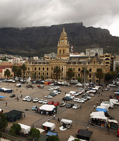 Cape Town's iconic Table Mountain looms behind the City Hall as the clock strikes noon above informal traders at the city's Grand Parade.