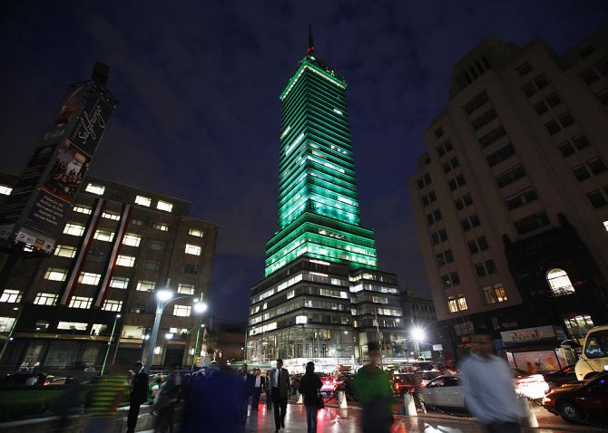 Pedestrians walk past the Torre Latinoamericana illuminated by LED lights, part of an artistic intervention, in downtown Mexico City.