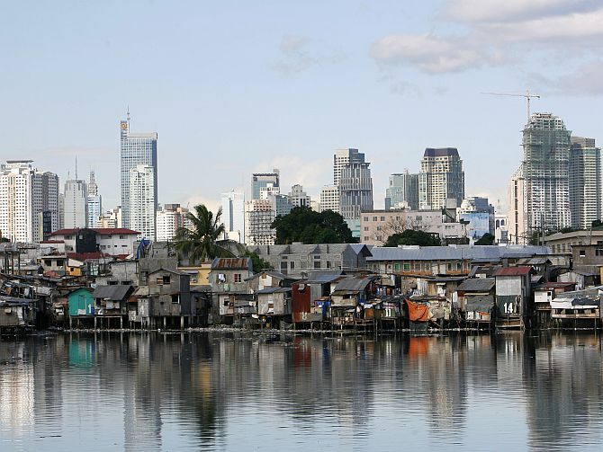 A shanty town is seen in front of the skyline of Manila's financial district of Makati City March.