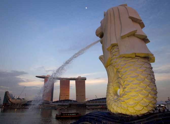 The Merlion statue overlooking the Marina Bay area spouts water as the Marina Bay Sands resort and casino is pictured in the background.