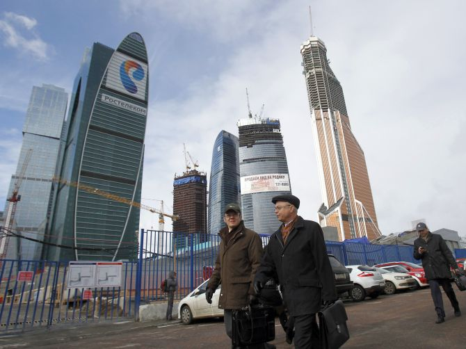 People walk as the Vostok or East tower (2nd R), part of the Federation complex in the Moscow City business district.
