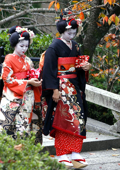 Women in traditional makeup and kimonos walk inside the Kiyomizudera temple during autumn in Kyoto.