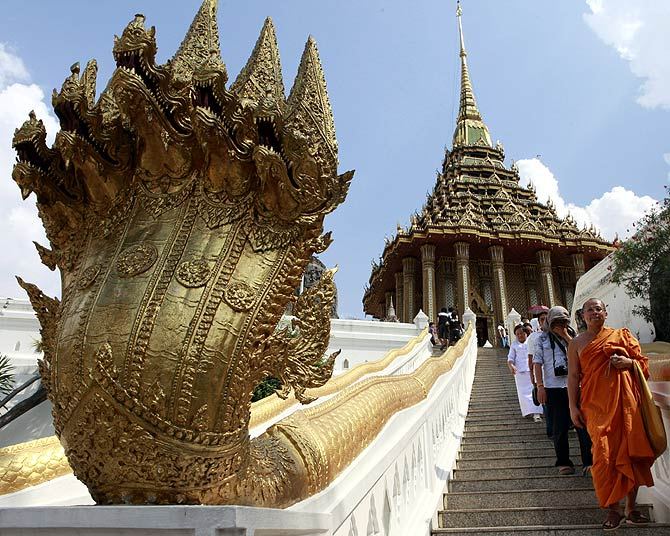 A Buddhist monk and people walk down a stairs during their visit at Wat Phra Phutthabat in Saraburi province.