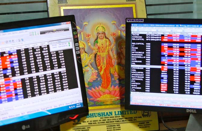 An image of Goddess Lakshmi is placed between monitors displaying share price index at a share trading market.