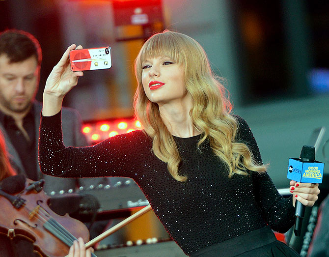 Singer and songwriter Taylor Swift takes a picture with her iPhone while peforming at ABC News' Good Morning America Times Square Studio.