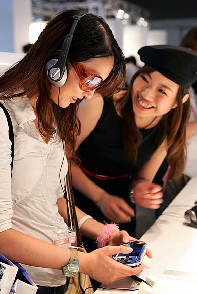 A woman plays Sony's PlayStation Portable (PSP) while a booth assistant (R) advises her during Tokyo Game Show.