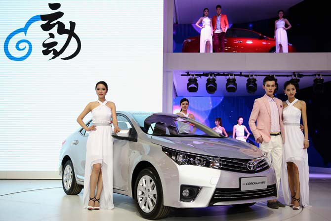 Models stand beside the Toyota Corolla cars during the 2014 Beijing International Automotive Exhibition.