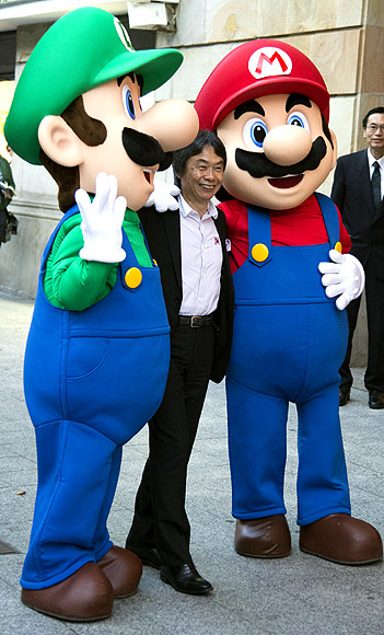 Japanese video game Designer Shigeru Miyamoto poses with men dressed as Mario Bros characters during a tribute in Gijon.