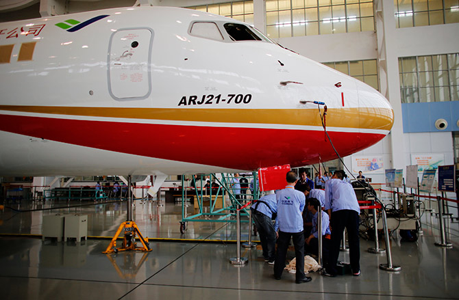 Technicians inspect a ARJ21-700 aircraft model at the Commercial Aircraft Corp of China Ltd (Comac) factory in Shanghai.