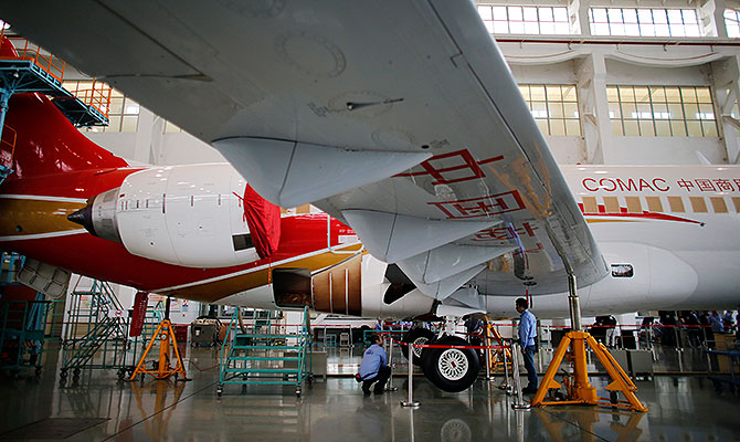 Technicians inspect a ARJ21-700 aircraft model at the Commercial Aircraft Corp of China Ltd (Comac) factory in Shangha3.