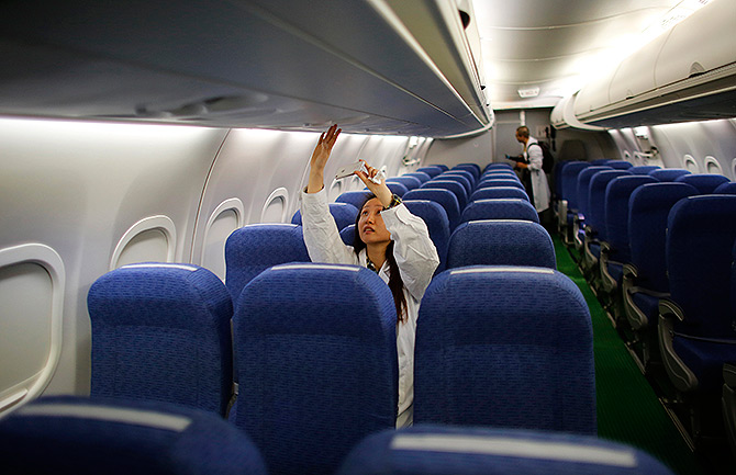 A journalist takes a picture with her mobile phone inside a ARJ21-700 aircraft.
