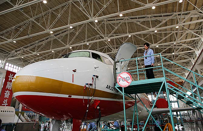 A technician inspects a ARJ21-700 aircraft model at the Commercial Aircraft Corp of China Ltd (Comac) factory in Shanghai.