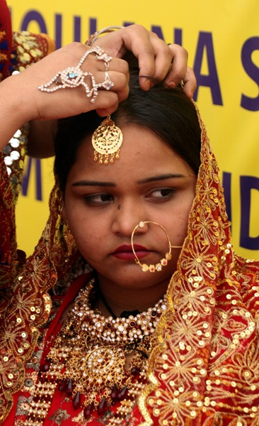 A bride is bedecked with jewellery during a mass wedding ceremony in Ahmedabad.