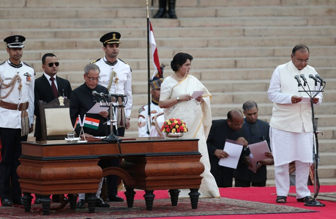 President Pranab Mukherjee (3rd L) administers the oath of office to Arun Jaitley (R) as a Cabinet minister at the Rashtrapati Bhavan in New Delhi May 26, 2014.