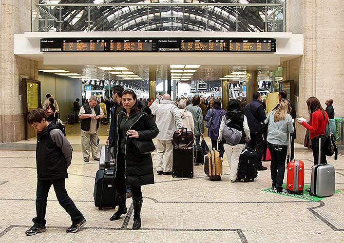 Passengers look at the departures board at Milano Centrale train station.