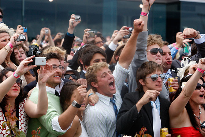 Race-goers celebrate as they watch jockey Corey Brown ride Shocking to victory in the Melbourne Cup at Flemington racecourse in Melbourne.