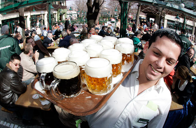 A waiter serves beer at the season opening of Vienna's Schweitzerhaus, a traditional beer garden at Vienna's amusement park 'Wurstl Prater'.