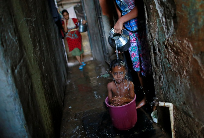 Four-year-old Manjunath takes a bath while sitting inside a bucket outside his house in a slum in Mumbai.