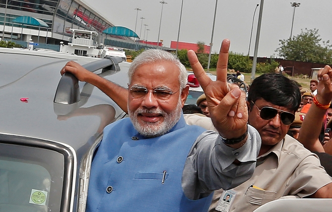 Prime Minister Narendra Modi gestures towards his supporters from his car.