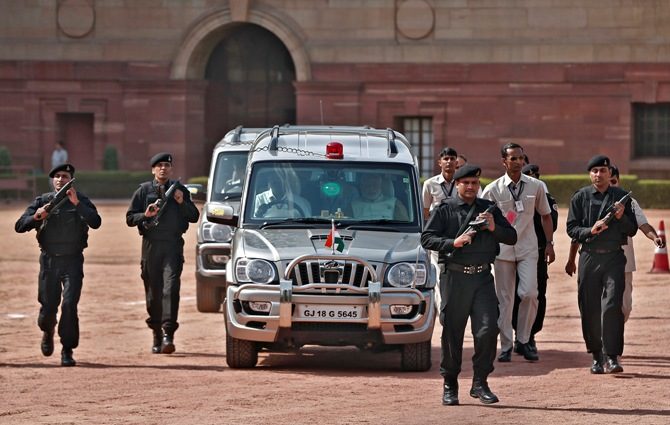 Prime Minister Narendra Modi (front R, in car), arrives to speak with the media after his meeting with President Pranab Mukherjee at the Rashtrapati Bhavan in New Delhi.