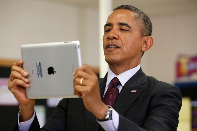 US President Barack Obama holds up an Apple iPad during a visit to Buck Lodge Middle School in Adelphi, Maryland.
