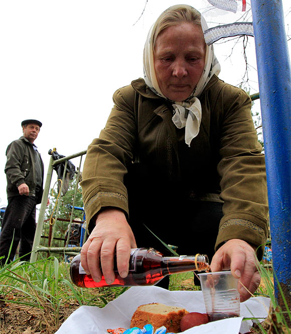 A woman fills a glass with wine at a grave in a cemetery during Radunitsa, or the Day of Rejoicing.