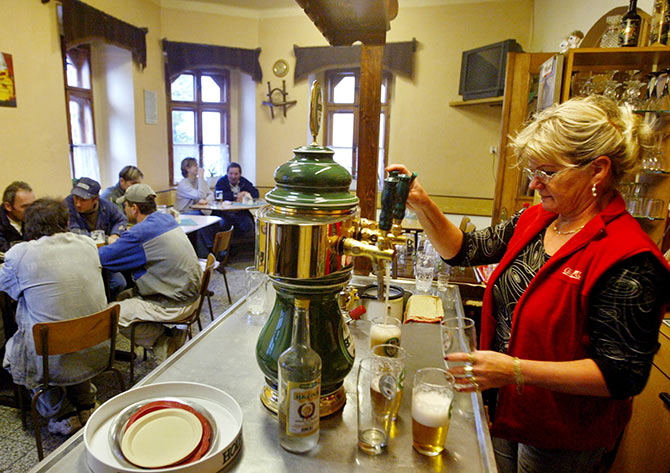 A woman serves beers in a bar in the Czech town of Horni Benesov.
