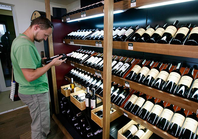 A man holds at a bottle of wine at a store of an industrial complex.