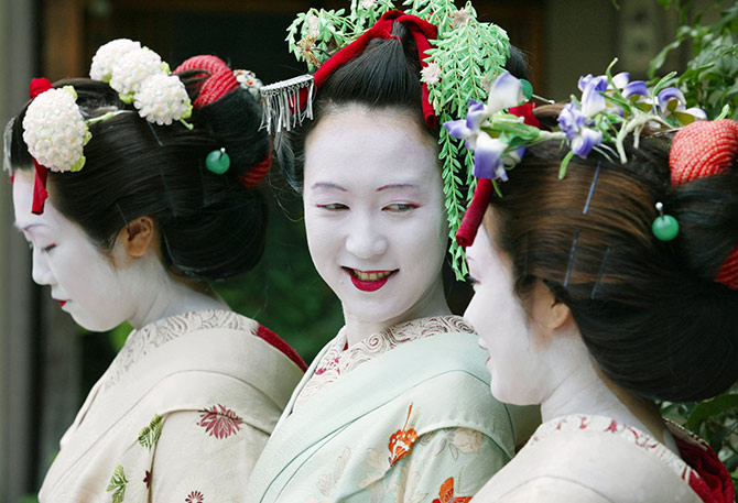 Japanese tourists Naomi Sato (L), Hitomi Abe (C) and Kumi Tamizane wear rented Maiko costumes in the ancient Japanese capital of Kyoto.