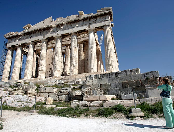 A tourist takes photos of the temple of Parthenon atop the ancient Acropolis in Athens.