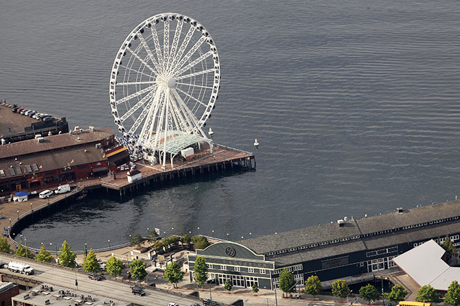 An aerial view shows the Seattle Great Wheel (top) and the Seattle Aquarium on the Elliott Bay waterfront.