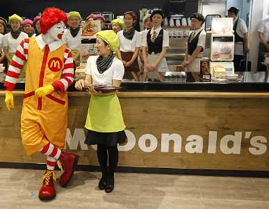 Image: McDonald's 'Ronald McDonald' character chats with a counter staff in Tokyo, Japan. Photographs: Kim Kyung-Hoon/Reuters