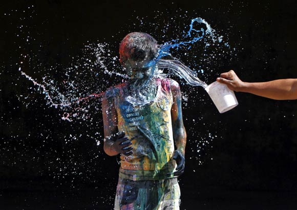 A man is splashed with colours during Holi