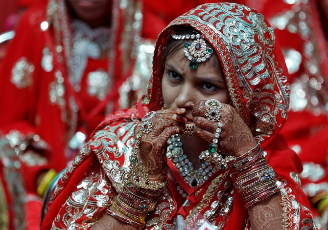 A bride adjusts her nose ring before taking her wedding wows during a mass marriage ceremony in Ahmedabad.