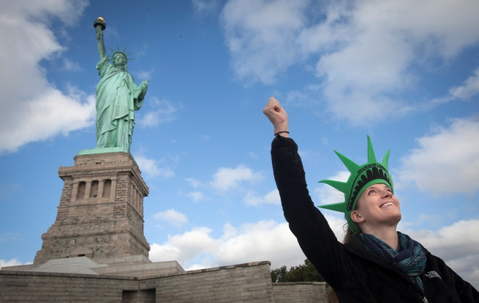 A tourist poses in front of the Statue of Liberty