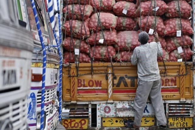 A labourer prepares to unload sacks of potatoes from a truck at a wholesale vegetable and fruit market in New Delhi.