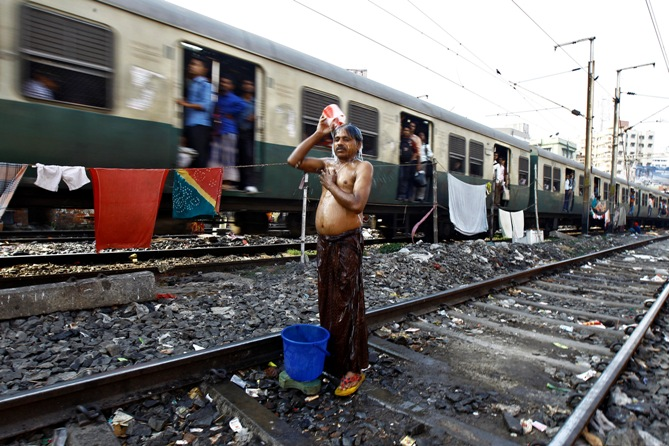 A man takes a bath on a railway track next to a train passing through a slum area
