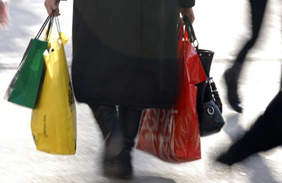 A woman carries shopping bags