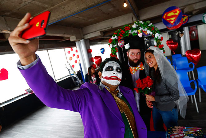 A man dressed as comic book character The Joker takes a selfie.