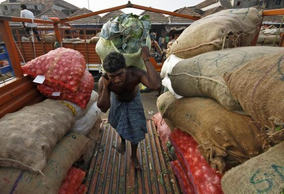 A labourer carries a sack filled with cabbage to load it onto a supply van at a vegetable wholesale market in Chennai.