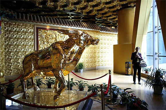 Image: A woman stands next to a gold statue of an ox. Photographs: Carlos Barria/Reuters