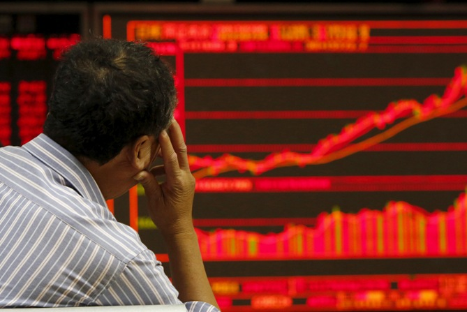 An investor watches an electronic board showing stock information at a brokerage office in Beijing, China, July 9, 2015.