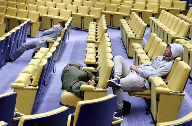 Reporters sleep in the press conference room of the European Council during an euro zone leaders summit in Brussels, Belgium, July 13, 2015.