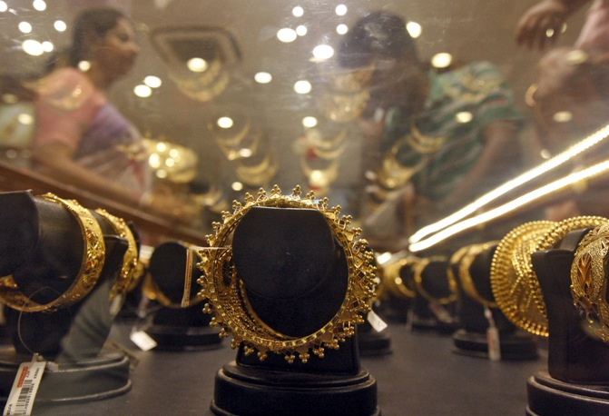 Image: Gold bracelets are on display as a woman (left) makes choices at a jewellery showroom on the occasion of Akshaya Tritiya, a major gold buying festival, in Kolkata. Rupak De Chowdhuri/Reuters