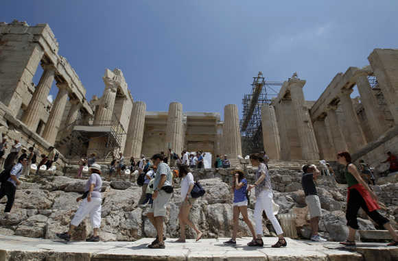 Tourists make their way in front of the Propylaia at the archaeological site of the Acropolis hill in Athens.